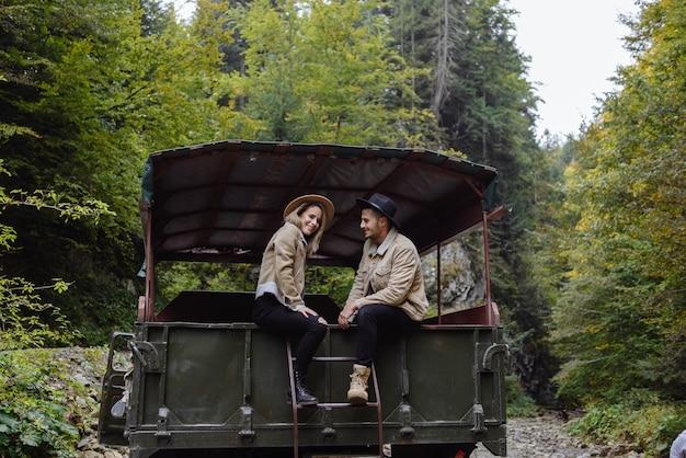 Een paar jonge mensen rijden zittend op de achterkant van de vrachtwagen. portret van reizigers op de achtergrond van het bos