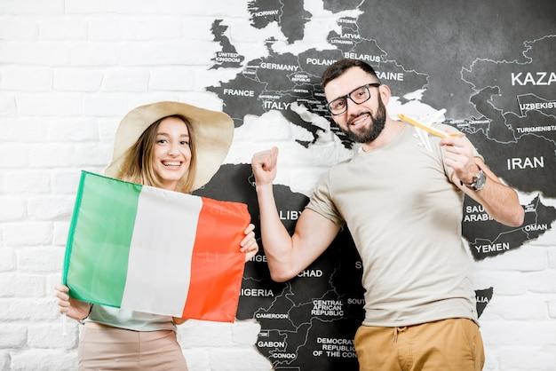 Een paar jonge reizigers die met een italiaanse vlag bij de muur staan met een wereldkaart, dromend over zomervakanties in italië