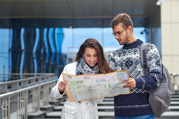 Een paar jonge toeristen die een kaart lezen en een locatie in de stad zoeken