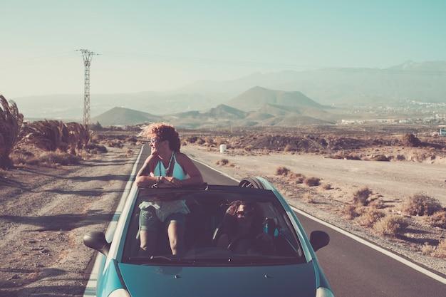 Een paar jonge volwassen vrouwen in een cabriolet rijden over een lange weg met woestijn
