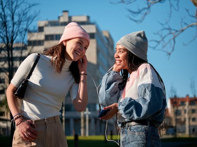 Een paar jonge vriendinnen die vrijetijdskleding dragen en een smartphone met oortelefoons gebruiken