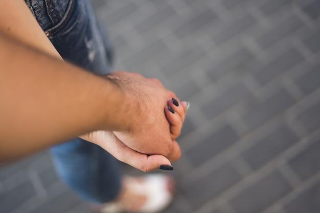 Een paar jonge vrouwen en jonge mannen houden elkaars hand vast
