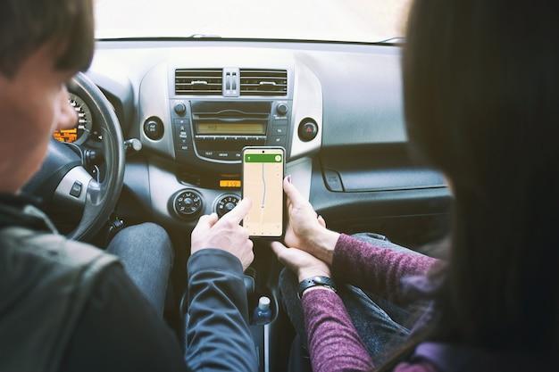Een paar jongeren rijden in een auto en kijken naar de gps-app op de smartphone