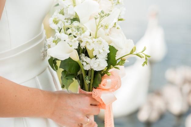 Een paar jonggehuwden met een boeket van witte rozen zit dichtbij het meer. zwaan zwemt