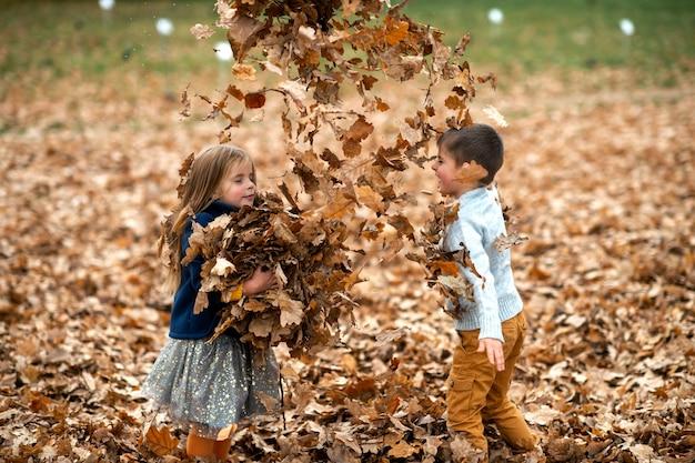 Een paar kinderen spelen met bladeren