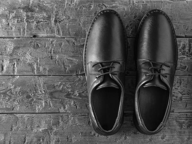 Een paar klassieke zwarte leren herenschoenen op een zwarte houten vloer. klassieke herenschoenen. het uitzicht vanaf de top.