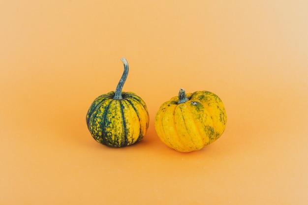 Een paar kleine pompoenen op gele achtergrond