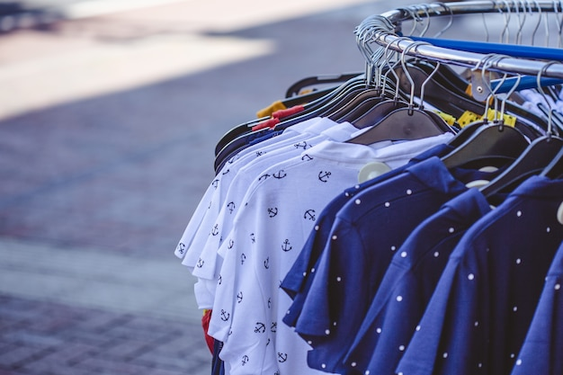 Een paar kleurrijke shirts aan kleerhangers op de stoep