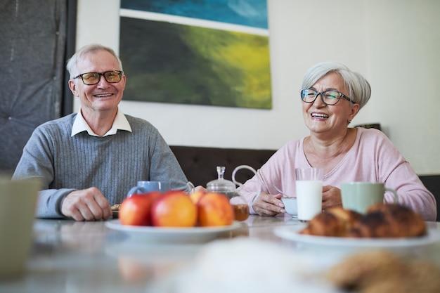 Een paar lachende senioren die genieten van het ontbijt aan de eettafel in de kopieerruimte van een verpleeghuis