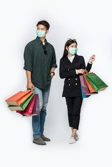 Een paar mannen en vrouwen droegen maskers en droegen veel papieren zakken om te winkelen