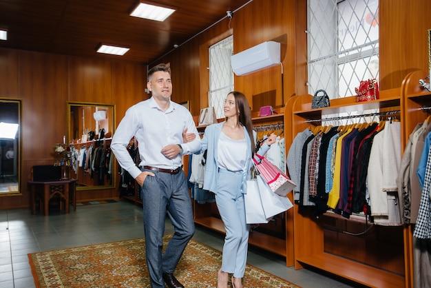Een paar mannen en vrouwen kiezen kleding in de winkel.