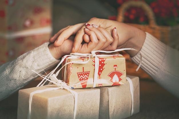 Een paar mensen geven elkaar kerstcadeaus verpakt in papieren handen close-up