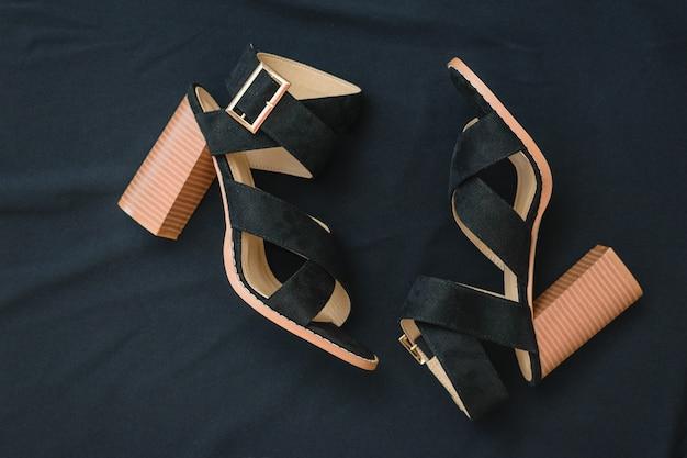Een paar modieuze damesschoenen met hoge hakken met zwarte stof. plat leggen.