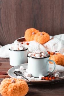 Een paar mokken met cacao en marshmallows, pompoenen en een warme trui op een houten tafel. verwarmende herfstzoete dranken. verticale weergave