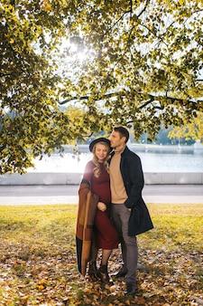Een paar mooie geliefden brengen tijd buiten door op de herfstdag, mooie vrouw in een rode jurk en mode...