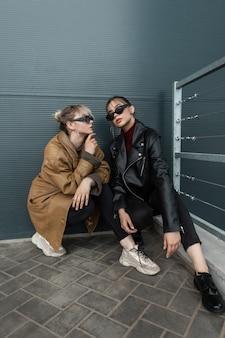 Een paar mooie jonge modellenmeisjes in modieuze leren jassen met zwarte jeans in stijlvolle schoenen zitten in de buurt van een metalen muur in de stad