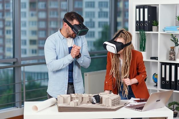 Een paar ontwerpers of ingenieurs analyseren de mock-up van een toekomstige woonwijk met behulp van een bril in