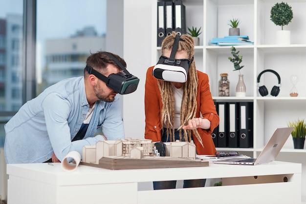Een paar ontwerpers of ingenieurs analyseren de mock-up van een toekomstige woonwijk met behulp van een veiligheidsbril in een architectenbureau.