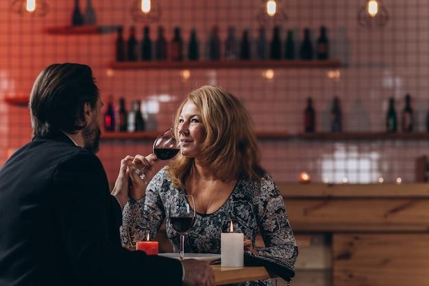 Een paar op middelbare leeftijd op valentijnsdag is bij kaarslicht aan het dineren in een restaurant