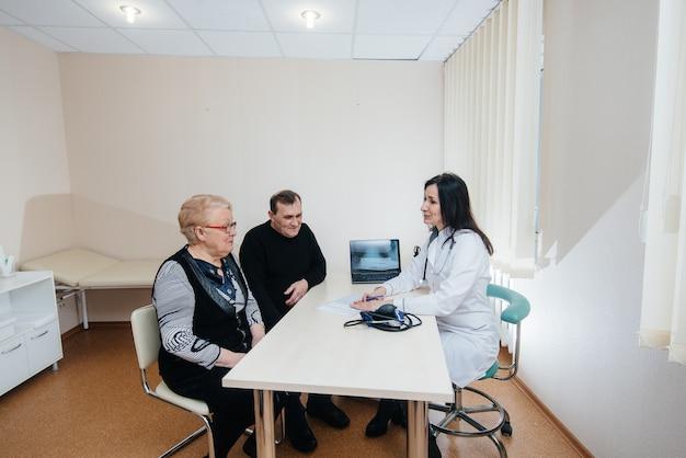 Een paar ouderen op afspraak van een huisarts in een medisch centrum. geneeskunde en gezondheidszorg.