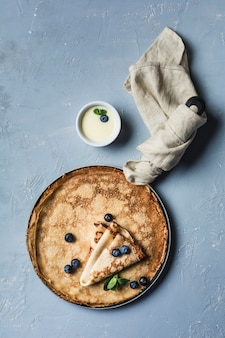 Een paar pannenkoeken in een pan met bosbessen en munt, met gecondenseerde zoete melk in een juskom