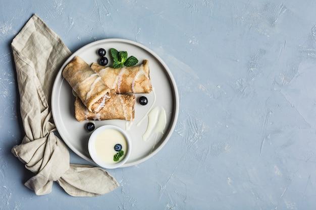 Een paar pannenkoeken met vulling op een grijze plaat met bosbessen en munt, met gecondenseerde zoete melk in een juskom op een lichtblauwe achtergrond.