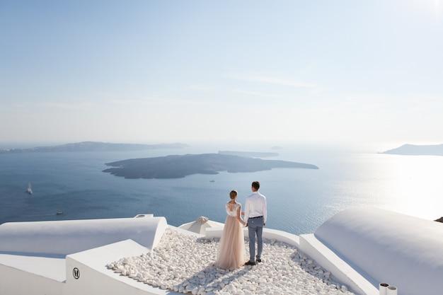 Een paar pas getrouwde mensen in prachtige kledij genieten van hun huwelijksreis in griekenland