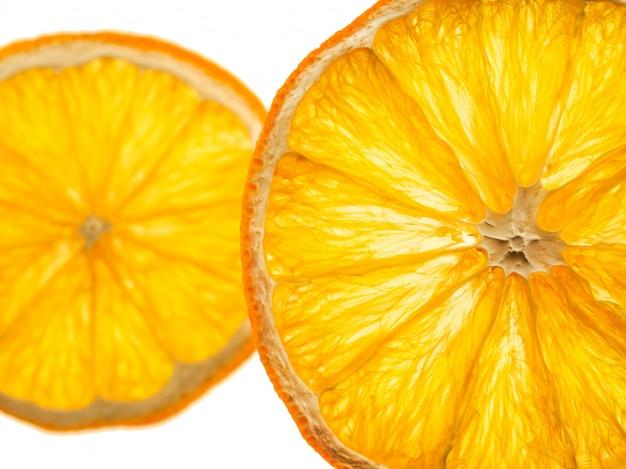 Een paar plakjes gedroogde sinaasappel op een witte achtergrond.