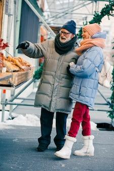 Een paar positieve gepensioneerden in winterjassen die voor de toonbank op de kermis staan en glimlachen terwijl ze naar een heerlijke bakkerij kijken