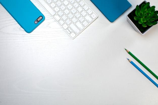 Een paar potloden draadloos toetsenbord en smartphone