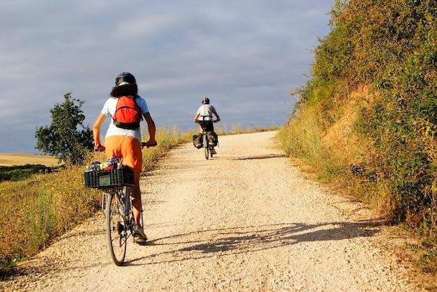 Een paar reizigers op een toerfiets die op een landelijke weg in spanje richting santiago de compostela reizen.