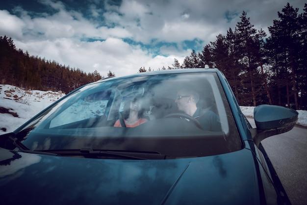 Een paar rijdt in de mooie auto op een besneeuwde winterdag.