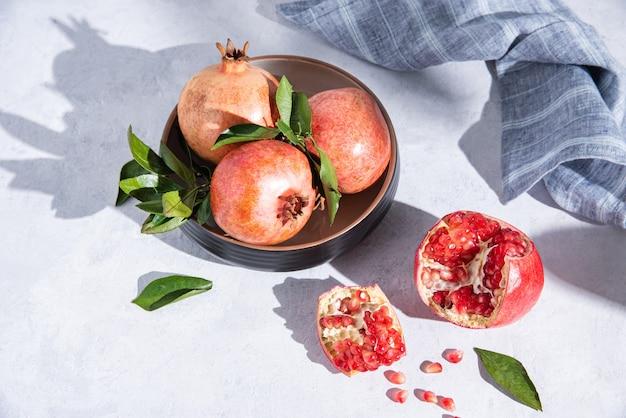 Een paar rijpe sappige granaatappels in een bord op een witte tafel in het ochtendzonlicht. bovenaanzicht
