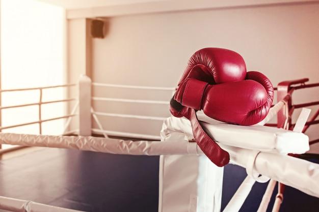 Een paar rode bokshandschoenen hangt van de ring