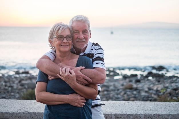 Een paar senioren die met veel liefde op het strand zwoegen - samen met pensioen - vrouw met bril en man met zeeachtergrond