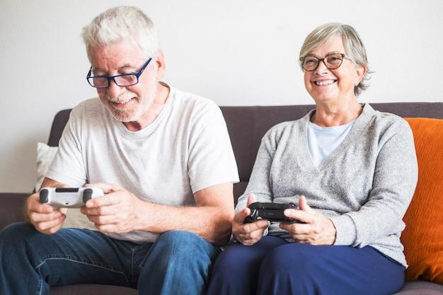 Een paar senioren die op de bank zitten en videogames spelen met een controller - mensen hebben plezier en genieten samen van lachen - binnen- en thuisconcept
