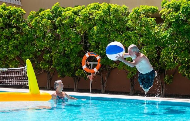 Een paar senioren die spelen in het blauwe en transparante water van het zwembad. man springt in het zwembad met een grote opblaasbare bal