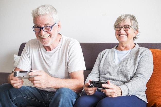 Een paar senioren die thuis vieogame spelen met joystick - binnenshuis genieten en plezier hebben met games - zittend op een bank - glimlachen
