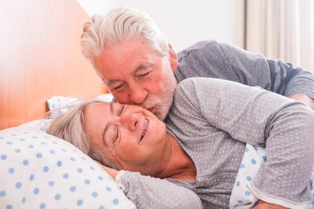 Een paar senioren die wakker worden en glimlachen met een knuffel terwijl ze thuis in bed liggen. hij kust haar met liefde voor een leven samen
