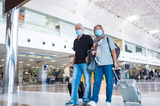 Een paar senioren en volwassen mensen lopen op een luchthaven met hun bagage en trolleys