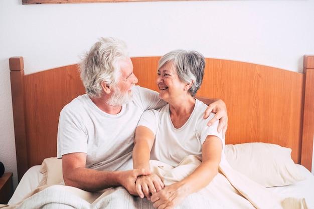 Een paar senioren kijken en glimlachen met liefde en affect terwijl ze hem kust - gepensioneerde en volwassen volwassenen die 's ochtends voor het opstaan in de slaapkamer zijn getrouwd