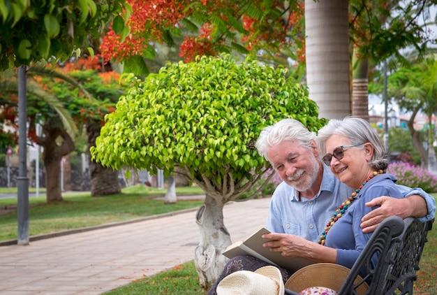 Een paar senioren ontspannen op een bankje in een openbaar park en lezen een boek gelukkig pensioenconcept