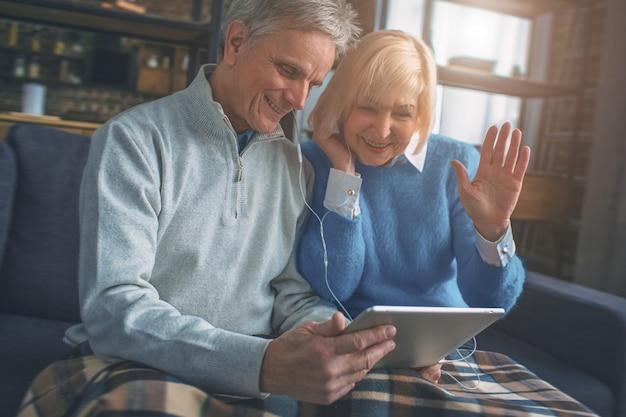 Een paar senioren praten met hun kinderen met behulp van technologie