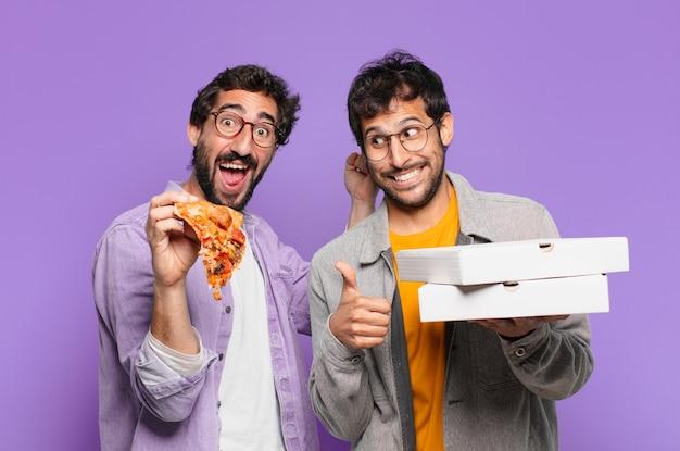 Een paar spaanse vrienden met een verbaasde uitdrukking en afhaalpizza's vasthouden?