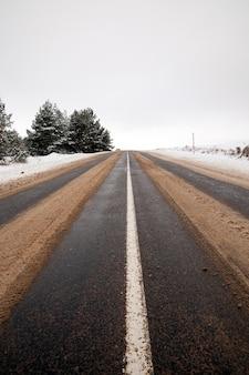 Een paar sporen op een asfaltweg van auto's die in de winter voorbij kwamen, smolt de sneeuw