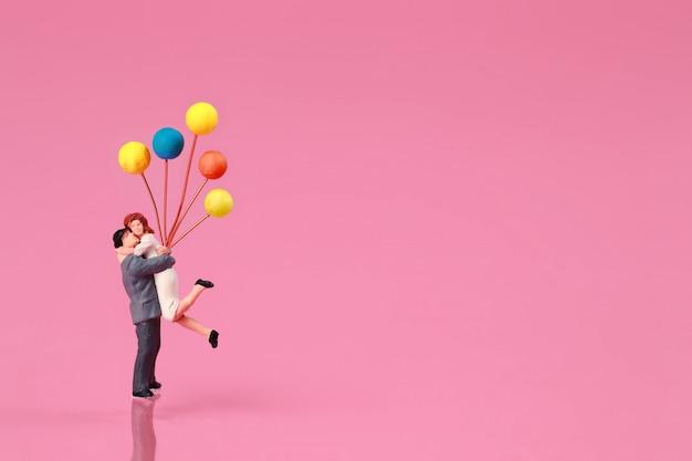 Een paar staande en ballon op roze te houden
