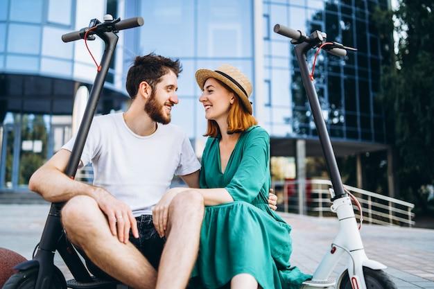 Een paar van twee aantrekkelijke mensen chillen in de buurt van het glazen gebouw met hun elektrische scooters. man en vrouw genieten van vakantie