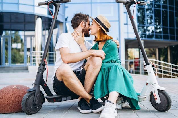 Een paar van twee aantrekkelijke mensen chillen in de buurt van het glazen gebouw met hun elektrische scooters.