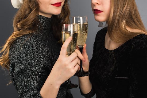Een paar van twee lesbiennes vieren graag kerstmis en nieuwjaar. twee gelukkige glimlachende meisjes die met champagneglazen roosteren