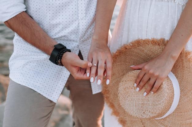 Een paar verliefd hand in hand een diamanten ring op de close-up van de meisjesvinger